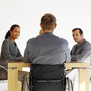 Themenfoto: Menschen sitzen bei einer Besprechung, einer davon im Rollstuhl