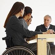 Themenfoto: Männer und Frauen bei einer Besprechung, eine Frau sitzt im Rollstuhl