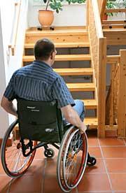 Foto: Ein Mann im Rollstuhl steht vor einer Treppe