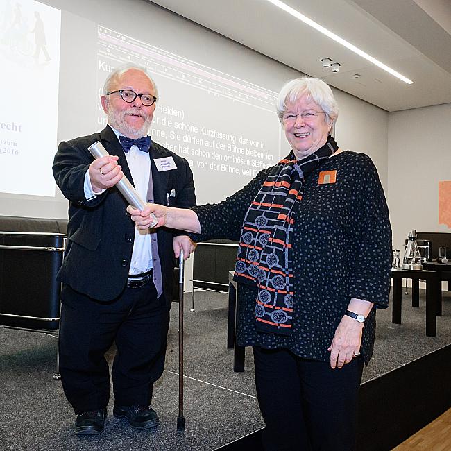 Ulrike Mascher übergibt symbolisch den DBR-Vorsitz an Volker Langguth-Wasem, indem sie ihm einen silbernen Staffelstab überreicht.