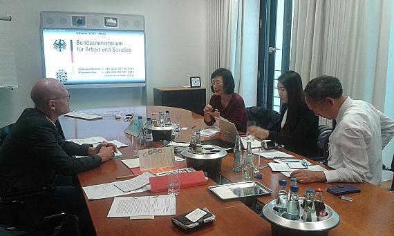 Das Foto zeigt die Teilnehmerinnen und Teilnehmer des Fachgesprächs an einem Tisch sitzend, sie unterhalten sich angeregt.