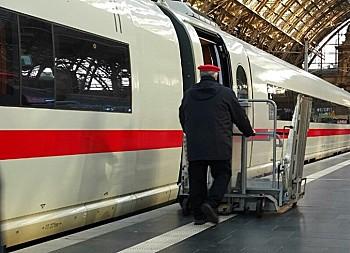 Ein Mitarbeiter der Deutschen Bahn bedient einen Hublift an einer geöffneten ICE-Tür