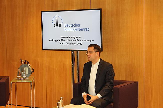 Das Foto zeigt Moderator Samuel Beuttler-Bohn, der auf einem Sofa sitzt