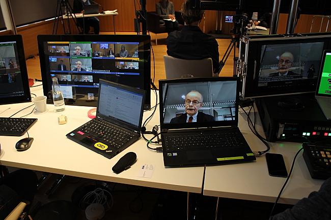Das Bild zeigt mehrere Notebooks mit der Live-Übertragung der Veranstaltung, auf dem Bildschirm ist Bernhard Franke zu sehen