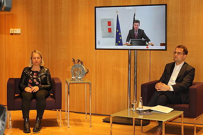 Hubertus Heil ist auf einem Bildschirm zu sehen. Links sitzt Verena Bentele, rechts Moderator Samuel Beuttler-Bohn.