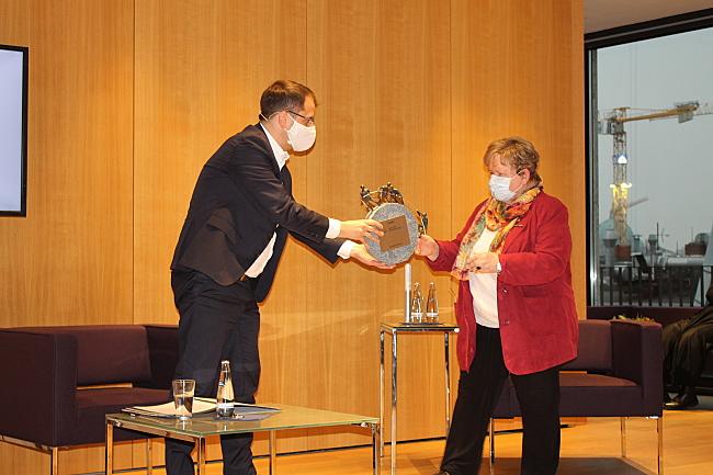 Samuel Beuttler-Bohn übergibt die Skulptur an Hannelore Loskill.