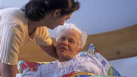 frau hilft einer alten pflegebed rftigen frau beim aufrichten im bett. Black Bedroom Furniture Sets. Home Design Ideas