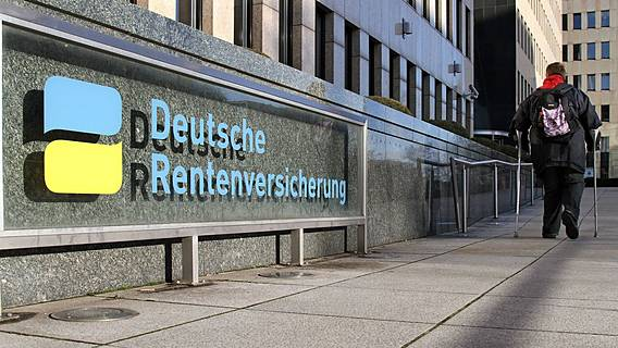 Symbolfoto: Gebäude der Deutschen Rentenversicherung, auf dem Gehweg davor geht eine Frau mithilfe eines Gehstocks.