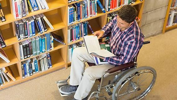 Symbolbild: Junger Mann im Rollstuhl in einer Bibliothek, er liest in einem Buch.