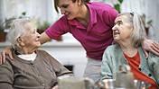 Symbolfoto: Zwei ältere Frauen sitzen in einem Pflegeheim an einem Tisch. Eine Altenpflegerin in einem pinken Poloshirt beugt sich über sie, legt die Arme um beide Damen.