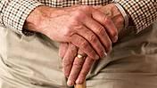 Die Hände eines alten Mannes stützen sich auf einen Gehstock.