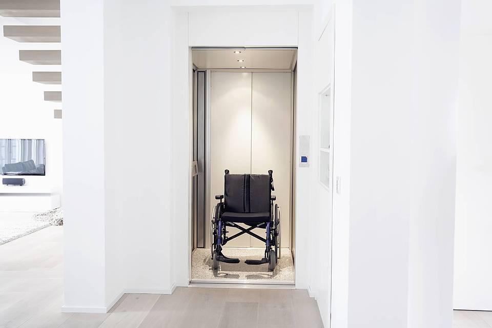 Symbolfoto: Ein Rollstuhl Steht In Einem Aufzug, Die Türen Sind Offen.  Blick In