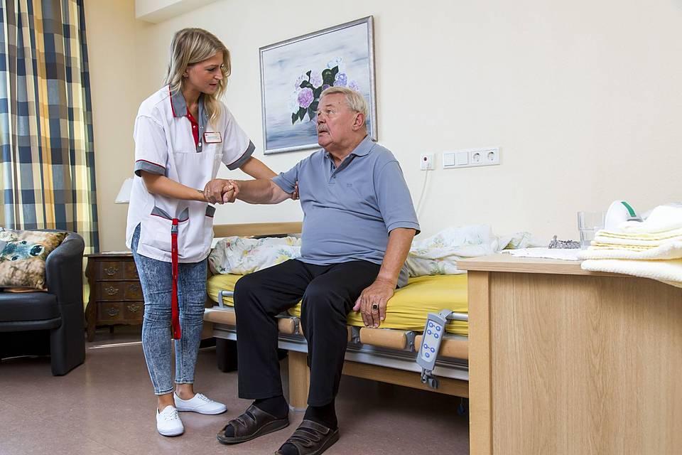 Symbolfoto: Eine Krankenpflegerin hilft einem älteren Mann beim Aufstehen aus dem Krankenbett.
