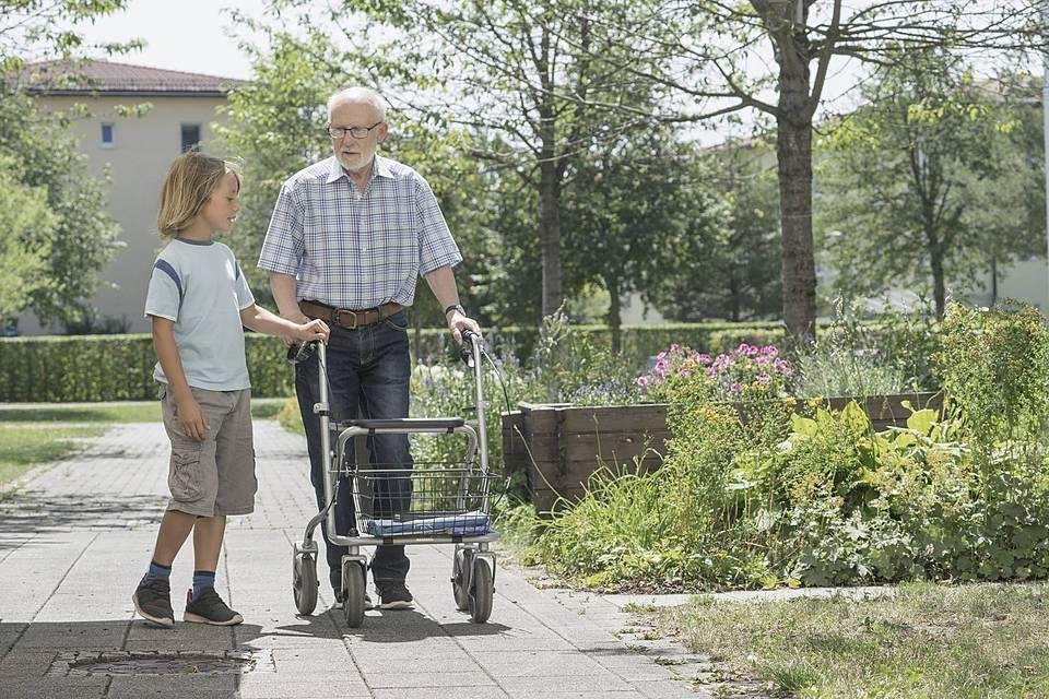 Ein Großvater mit Rollator und sein Enkel gehen spazieren.
